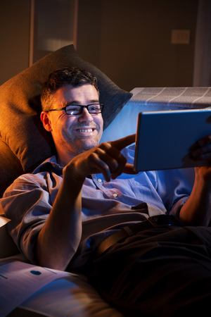 night shirt: Man working at night lying down on sofa in the living room with tablet. Stock Photo