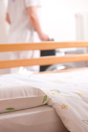 Bed at nursing home with nurse and wheelchair on background. photo