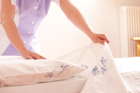 Woman making bed and changing bedding in guest room. photo
