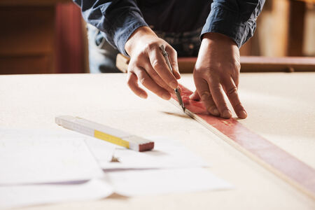 precise: Carpenter measuring and tracing lines with a ruler on a wooden surface.