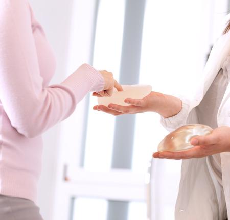 beaux seins: Docteur montrant implants mammaires de la patiente.