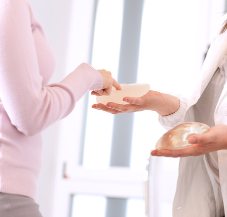 breasts: Doctor showing breasts implants to female patient. Stock Photo