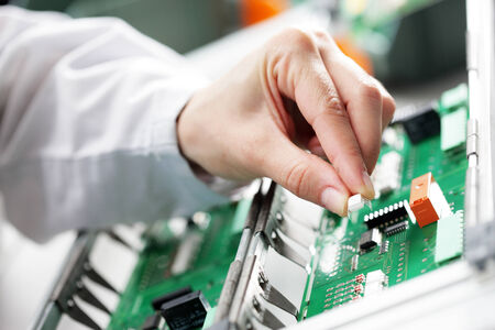 Technician assembling electonic components at his worktable. photo