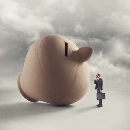 Businessman with briefcase contemplating a huge clay coin bank with sky on background. photo