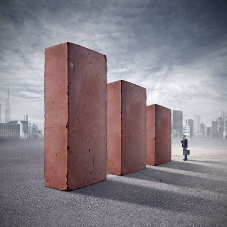 Businessman staring at huge standing bricks with skyline and clouds on background. photo