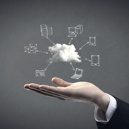 it tech: Hand drawn technology and computer icons around cloud with hand on gray background, cloud computing concept. Stock Photo