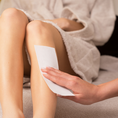depilaciones: Mujer que recibe un tratamiento de depilaci�n con cera en las piernas en el spa. Foto de archivo