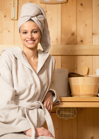 Young attractive woman smiling and relaxing in sauna at spa.