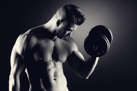 Muscular attractive man weightlifting on dark background. photo