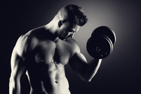 Muscular attractive man weightlifting on dark background. photo
