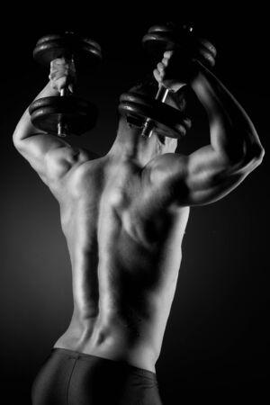 back training: Muscular attractive man weightlifting on dark background.