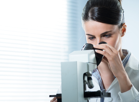 Young female researcher using microscope in the laboratory close up. photo