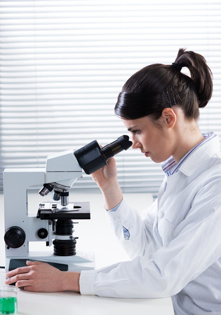 Female researcher analyzing samples with microscope in the laboratory. photo