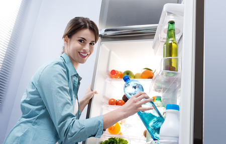 Young woman taking a water bottle from refrigerator and smiling at camera. photo