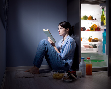 Sleepless woman sitting on the kitchen floor reading a book and eating. photo