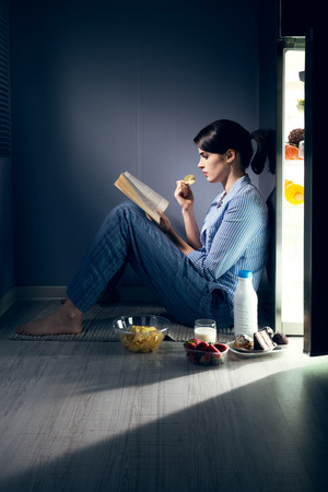 binge: Sleepless woman sitting on the kitchen floor reading a book and eating. Stock Photo