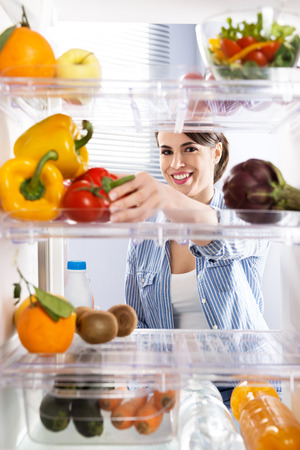 refrigerator with food: Young woman taking fresh healthy vegetables from refrigerator. Stock Photo