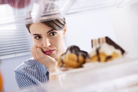 refrigerator with food: Young hungry woman in front of refrigerator craving chocolate pastries.