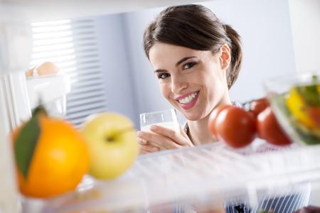 full: Atractiva mujer sonriendo y sosteniendo un vaso de leche delante de nevera. Foto de archivo
