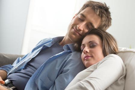 pareja durmiendo: Pareja joven amante durmiendo en el sofá en la sala de estar.