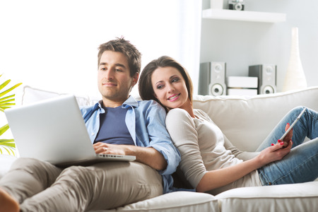 man couch: Young couple relaxing on sofa with digital tablet and laptop.