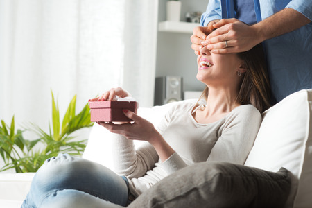Young woman receiving a surprise gift box from her boyfriend at home. Stock Photo