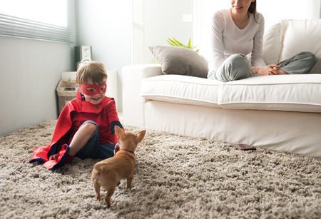 Cute super hero child and mother spending time together in the living room playing with dog.
