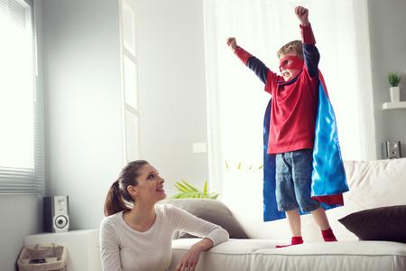 happy young: Madre que mira a poco de s�per h�roe con los pu�os levantados de pie en el sof�. Foto de archivo