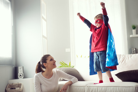 home family: Mother looking at little super hero with fists raised standing on sofa.
