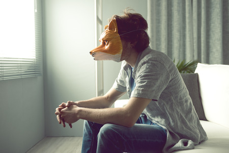 embarassment: Young man wearing a fox mask sitting on sofa in front of a window.