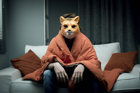 Young man wearing a fox mask sitting on sofa covered with a blanket. photo