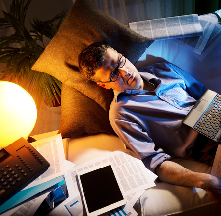 work break: Tired businessman sleeping on sofa at home surrounded by paperwork.
