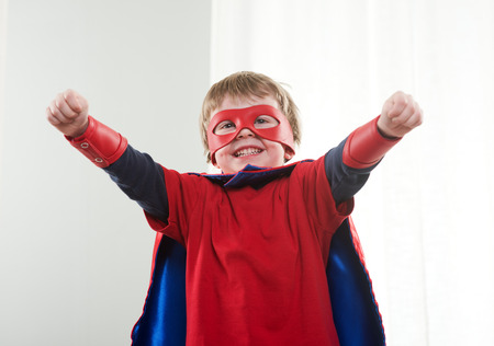 superpowers: Superhero boy standing  with arms raised showing his superpowers.