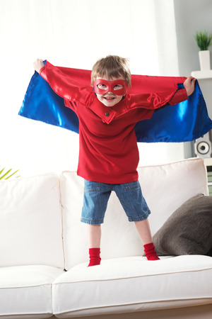 superpowers: Superhero boy standing on sofa with arms raised showing his superpowers. Stock Photo