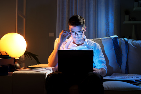 Businessman working on laptop at home on sofa until late.