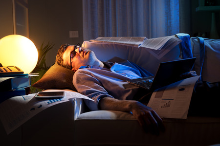 workaholic: Tired businessman sleeping on sofa at home surrounded by paperwork.