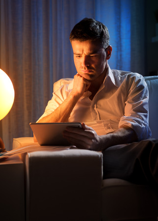 workaholic: Businessman working overtime late at night in the living room, with tablet and paperwork.