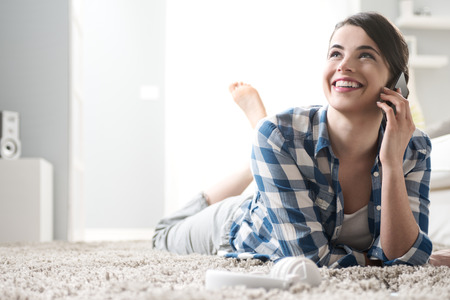 Smiling woman on the phone lying down on carpet in the living room. photo