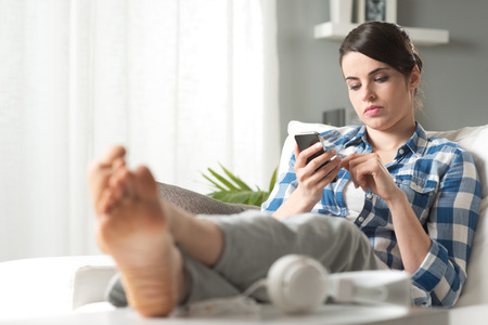 Attractive pensive woman lying on sofa and using mobile in the living room. photo