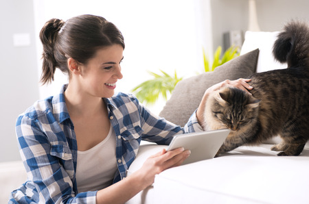 Smiling woman with tablet and beautiful cat in the living room. Banco de Imagens