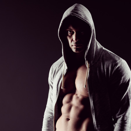 Body builder in hooded shirt with bare chest. photo