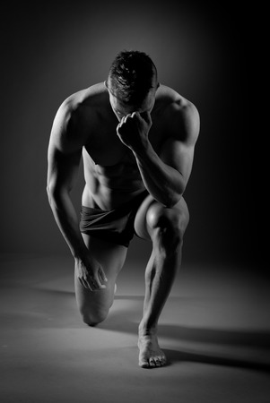 Body builder posing and showing off bicep muscle on dark background. photo