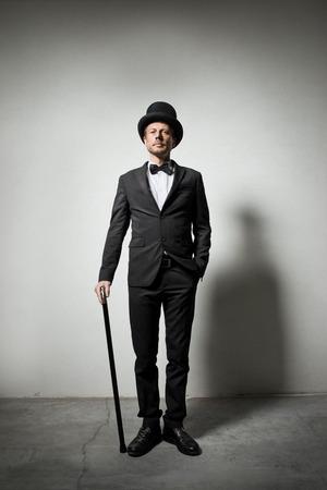hombre con sombrero: Caballero con clase con bombín y bastón mirando con confianza a la cámara. Foto de archivo