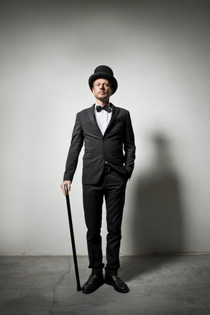 high society: Classy gentleman with bowler hat and cane looking confidently at camera. Stock Photo