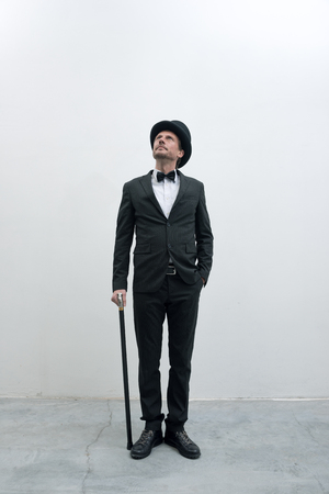 Classy gentleman standing on white background and concrete floor in elegant suit with cane and bowler hat, looking up. photo