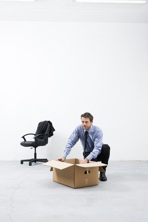 looking around: Businessman looking around and packing with cardboard box in an empty office.