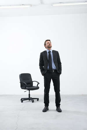 looking around: Smiling businessman standing in his new empty office with hands in pockets looking around. Stock Photo