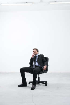 open plan: Businessman sitting in his new empty office looking around with hand on chin.