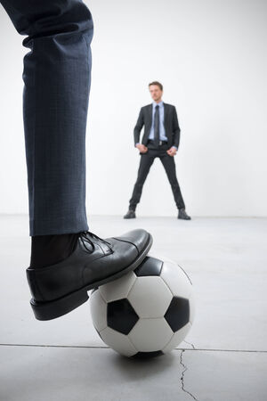 goal kick: Businessmen playing soccer in an empty room, ball and foot close up with goalkeeper on background.