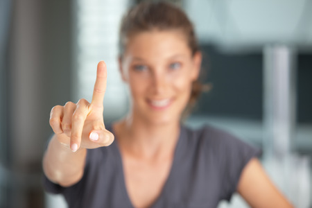 pointing finger: Young woman smiling and using a touch screen interface.